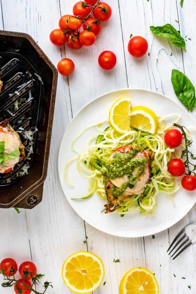 Photo of Keto Pesto Chicken sitting on a bed of zucchini noodles on a white plate with lemon and cherry tomatoes on the plate and a cast iron skillet next to it.