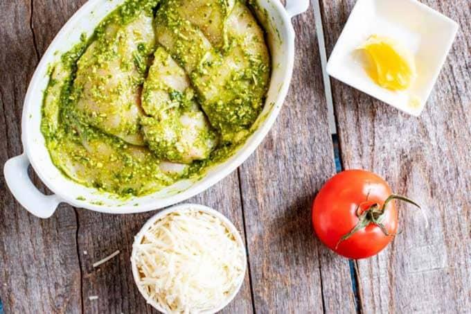 Photo of chicken breasts in a shallow dish marinating in pesto.