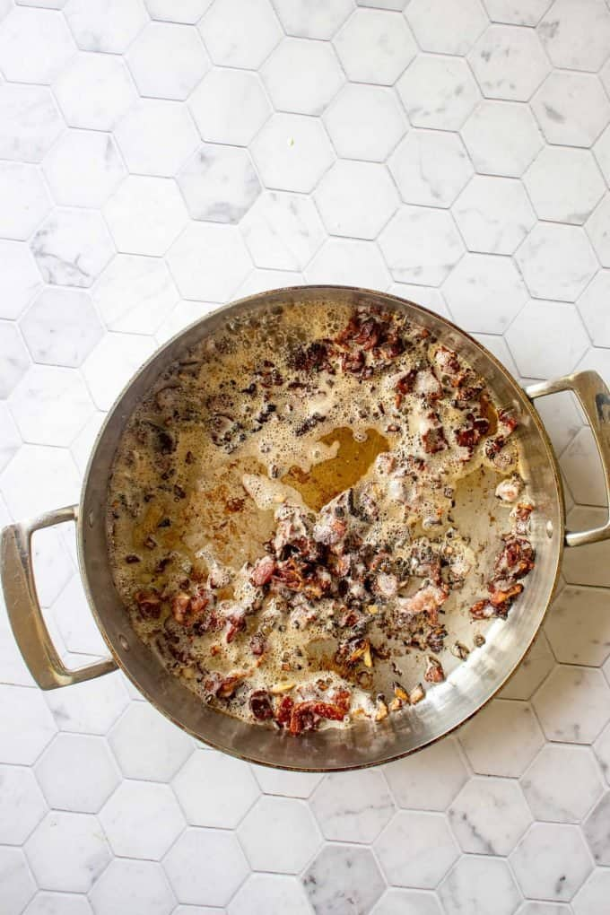 Photo of bacon and onion in a skillet.