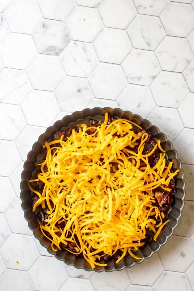 Photo of bacon and onion topped with cheese.