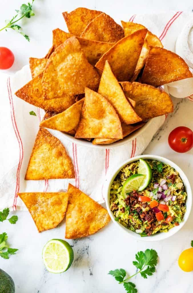 Overhead photo of a bowl of keto guacamole surrounded by low carb tortilla chips.
