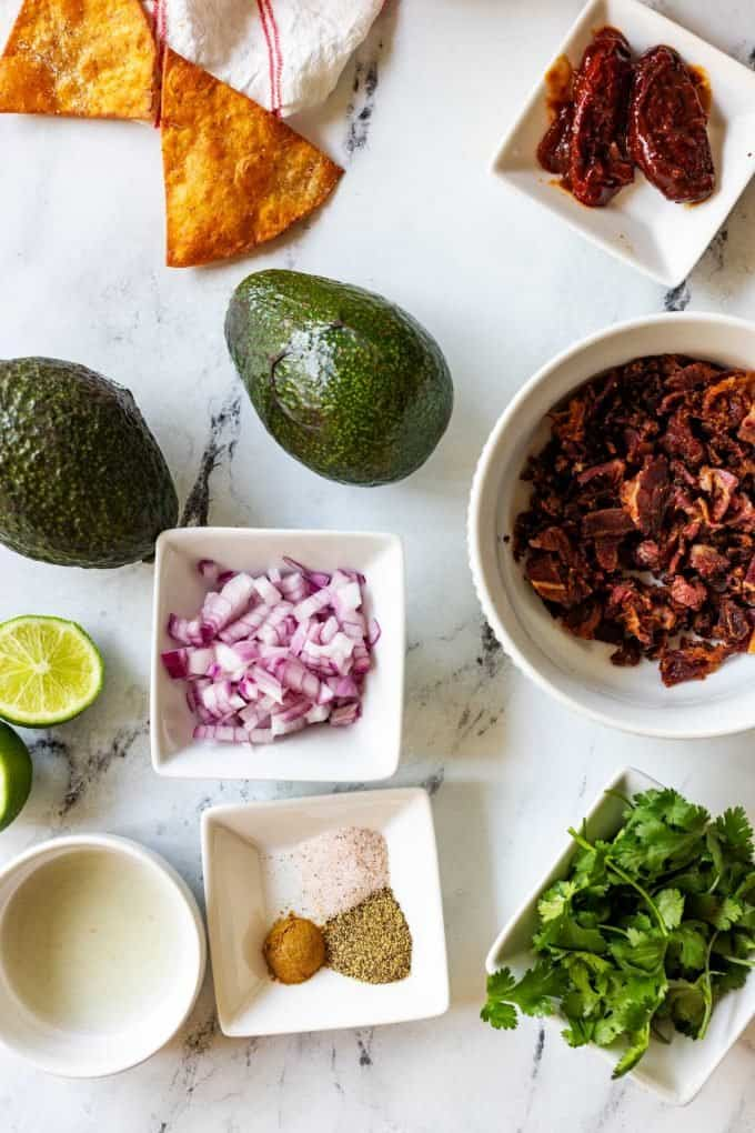 Photo of two avocados surrounded by lime juice, seasonings, bacon, onion, cilantro, and chipotle chiles in adobo sauce.