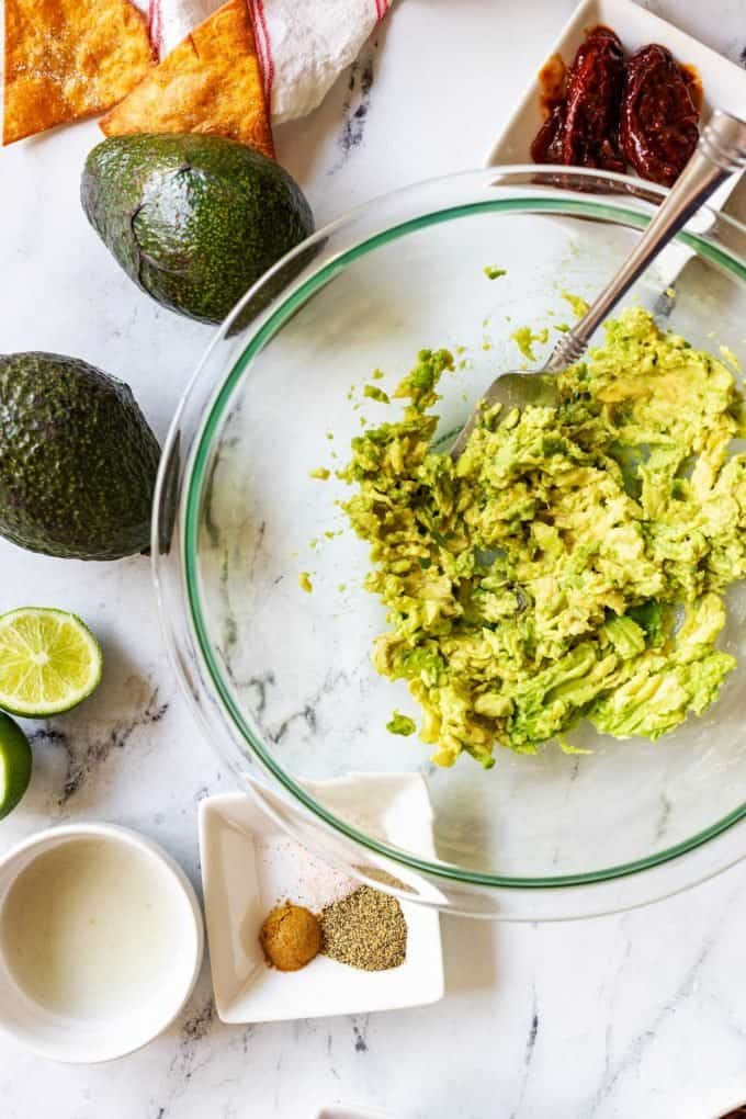 Photo of avocado in a bowl that has been mashed with a fork.