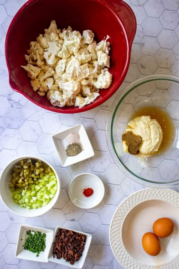 Overheat photo of a bowl of cauliflower and bacon, seasonings, chives, pickles, celery, eggs, and dressing in prep bowls..