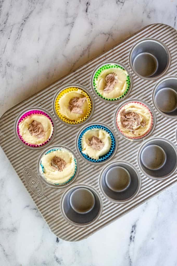 Photo of a muffin tin filled with vanilla cheesecake batter and topped with a small amount of chocolate cheesecake batter.