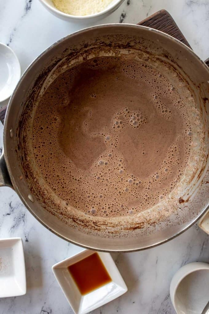 Photo of a sauce pan with heavy cream, cocoa powder, sweetener, and salt that has been added to it.