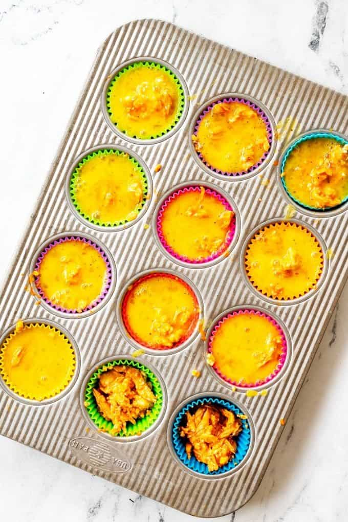 A muffin tin with quinoa egg muffins being made in it.