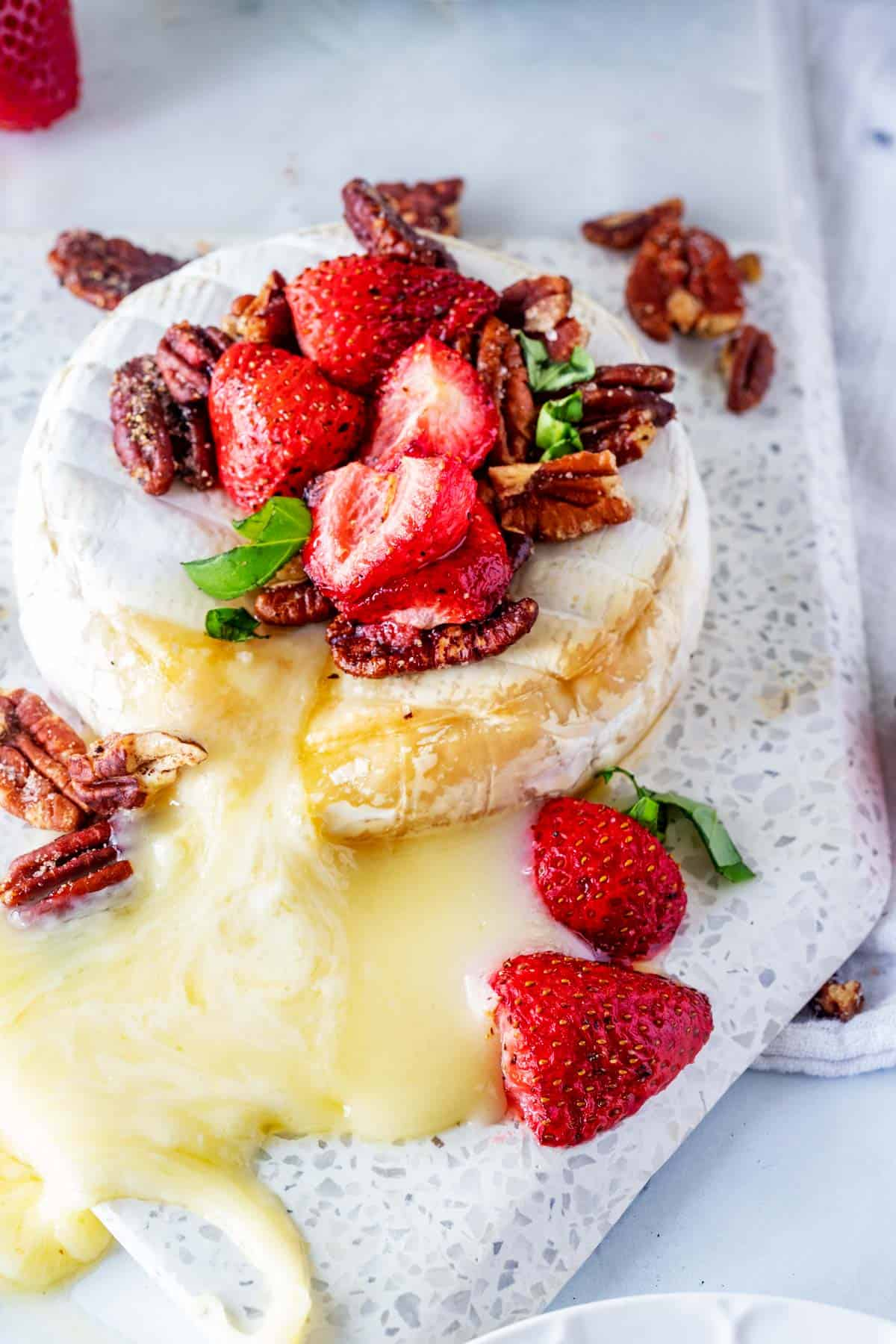 Close up photo of keto baked brie topped with strawberries and pecans.