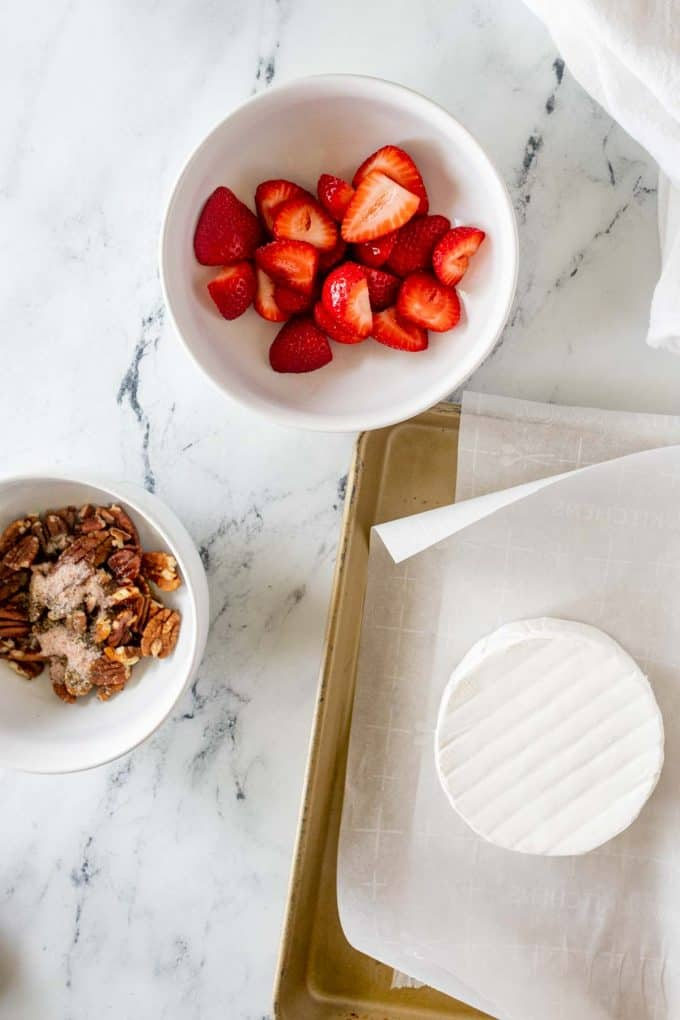 Photo of separate bowls of strawberries and pecans being tossed with salt and pepper.