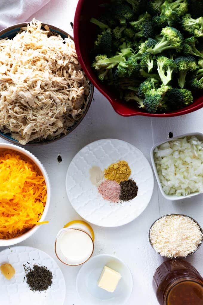 Overhead photo of prep bowls and dishes with broccoli, cooked chicken, cheese, onion, seasonings, cream, parmesan, butter, and broth.