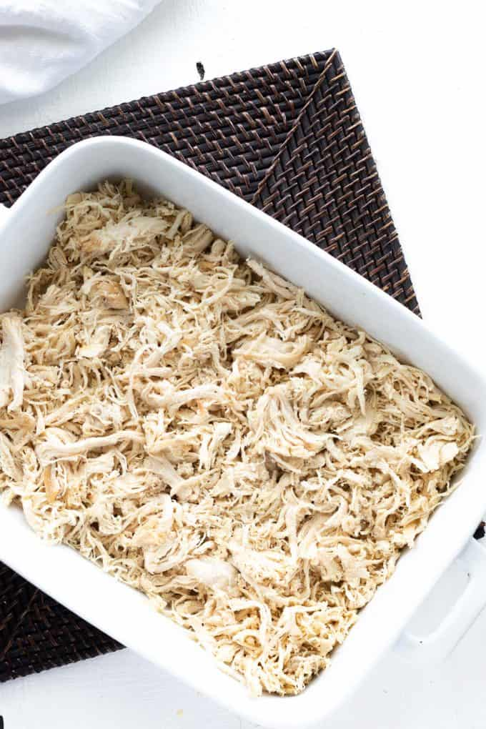 Photo of a white casserole dish with shredded chicken.