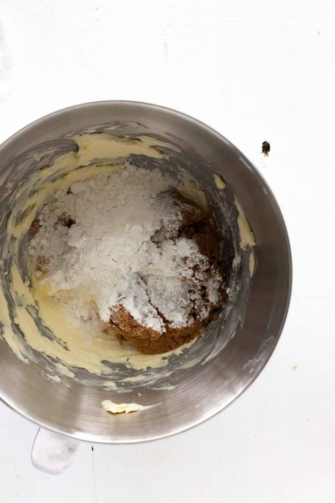 Photo of dry ingredients being added to butter that has been whipped for cookie batter.