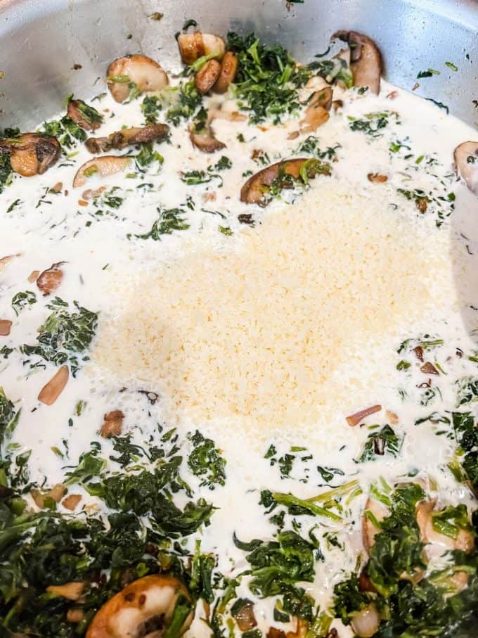 Photo of cream and parmesan cheese being added to a skillet of mushrooms and spinach.