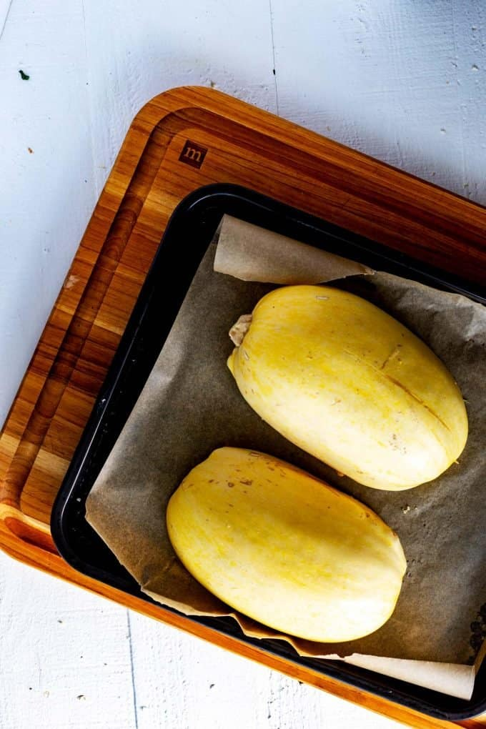 Photo of a spaghetti squash on a baking sheet ready to go in the oven.
