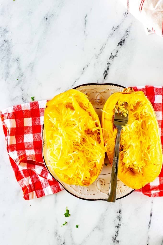 """Photo of a cooked spaghetti squash being turned into """"noodles"""" with a fork."""